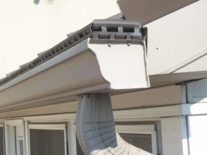 white gutter and downspout needing repair