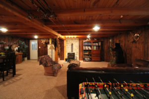 fully furnished basement with wooden accents