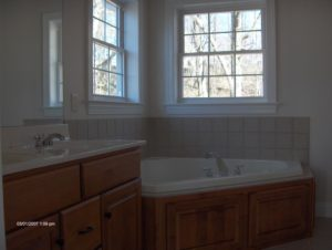bathroom remodeling with new bathtub and wooden cabinets