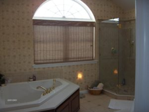 bathroom remodel with white tub and large windows