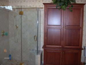 bathroom renovation with clear shower and wood cabinet