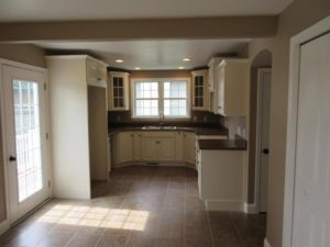 kitchen remodel with tan cabinets and light wooden floor