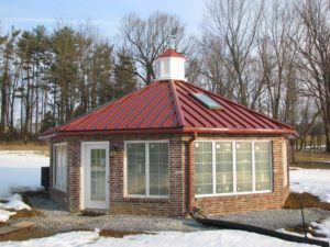 custom sunroom with red metal roof and pergola