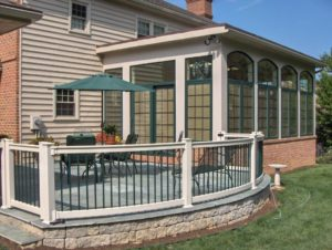 new stone patio with railing and attached sunroom